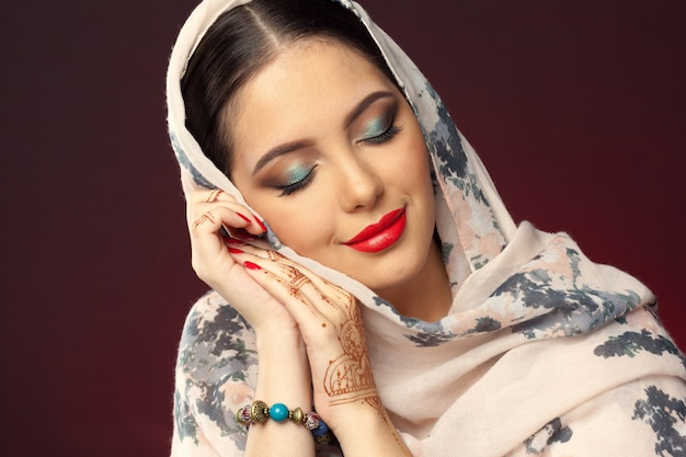 Mulher bonita em estilo oriental com mehendi em fundo escuro Foto Premium