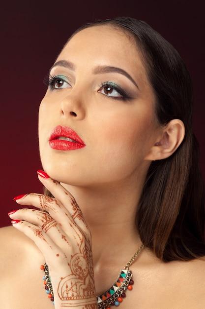Mulher bonita em estilo oriental com mehendi no escuro Foto Premium