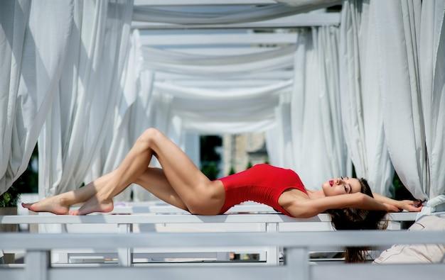 d7c6e340a Mulher bonita em maiô vermelho está no sofá branco fora