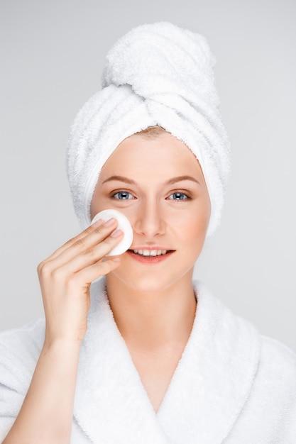 Mulher bonita em maquiagem de decolagem de roupão com esponja Foto gratuita