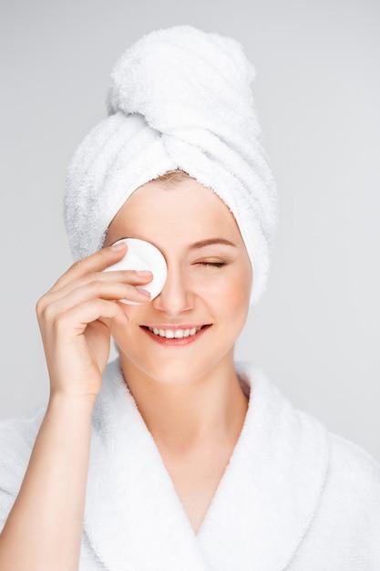 Mulher bonita em maquiagem de decolagem de roupão de banho com limpador Foto gratuita