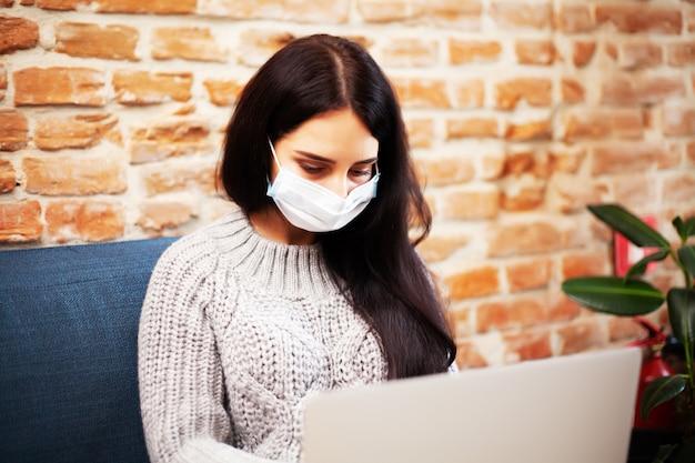 Mulher bonita em máscara no rosto, trabalhando no laptop em casa durante a pandemia Foto Premium