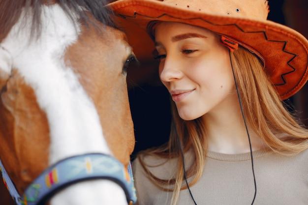 Mulher bonita em pé com um cavalo Foto gratuita