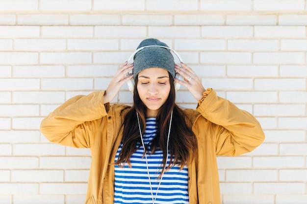 Mulher bonita em pé contra a parede de tijolos brancos usando fones de ouvido Foto gratuita