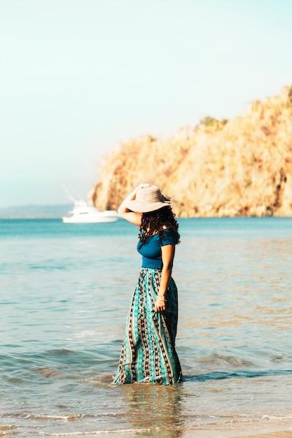 Mulher bonita em pé de chapéu na onda costeira na praia Foto gratuita