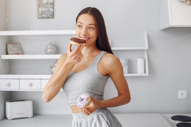 Mulher bonita em pé em uma cozinha com rosquinha Foto gratuita
