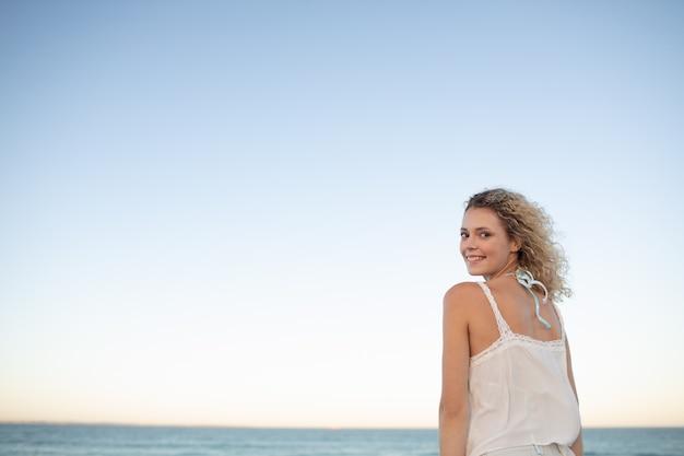 Mulher bonita em pé na praia Foto gratuita