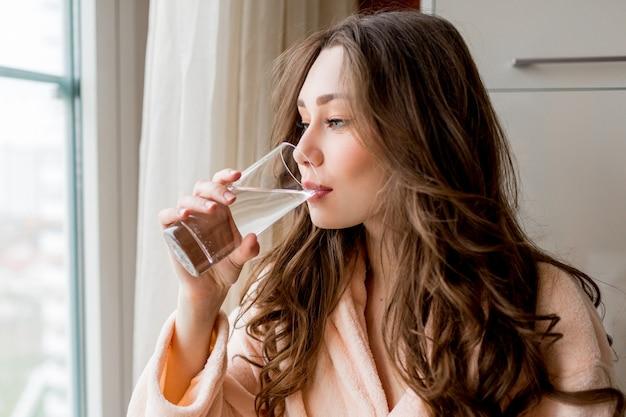 Mulher bonita em roupão de banho bebendo água doce em casa Foto gratuita