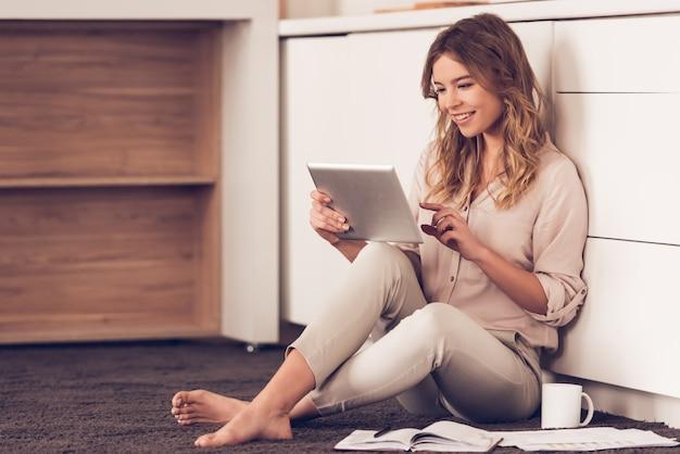 Mulher bonita em roupas casuais está usando um tablet digital Foto Premium