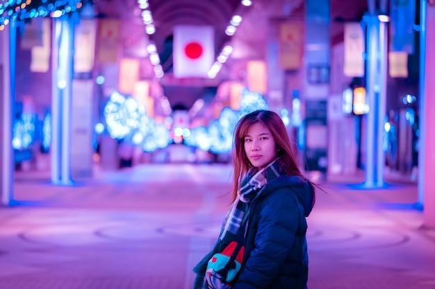 Mulher bonita em roupas de moda inverno na rua do japão à noite. Foto Premium