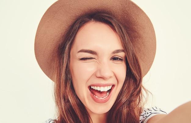 Mulher bonita em roupas de verão hipster tirar selfie de mãos com telefone Foto gratuita