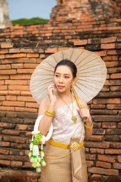 Mulher bonita em traje tradicional tailandês antigo, retrato no antigo templo de ayutthaya Foto gratuita