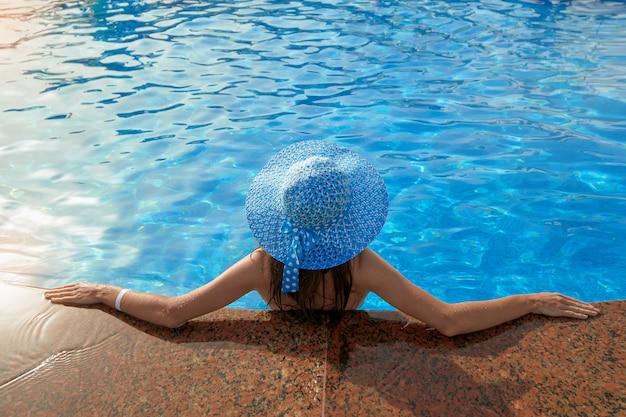 Mulher bonita em um chapéu sentado na beira da piscina Foto Premium
