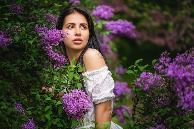Mulher bonita em um jardim de primavera com lilases florescendo Foto Premium
