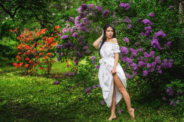 Mulher bonita em um jardim de primavera debaixo de uma árvore florescendo Foto Premium