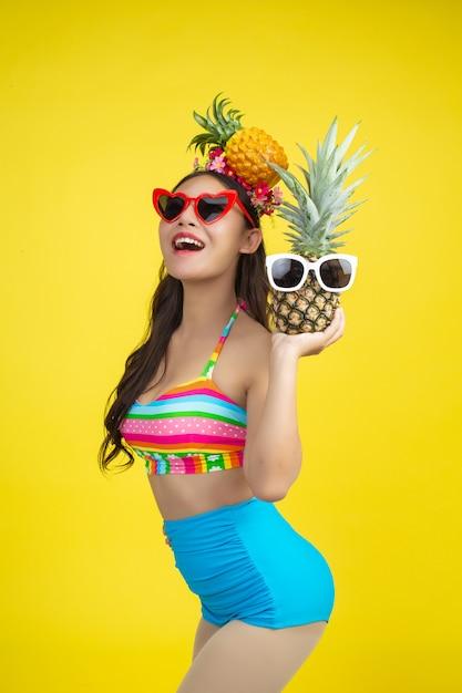 Mulher bonita em um maiô segurando um abacaxi poses em amarelo Foto gratuita