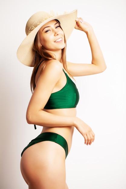 Mulher bonita em um maiô verde posando Foto Premium