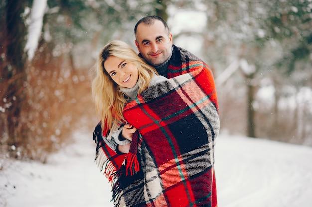 Mulher bonita em um parque de inverno com o marido Foto gratuita