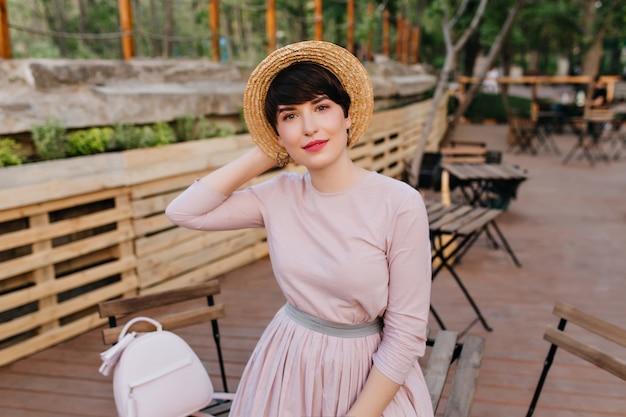 Mulher bonita em um vestido antiquado com uma mochila da moda posando alegremente em um café ao ar livre com mesas Foto gratuita