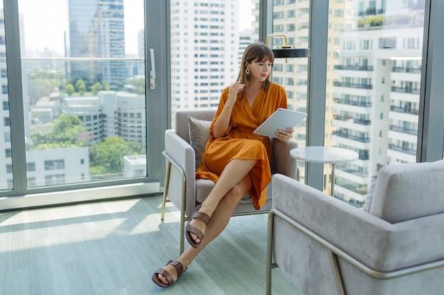 Mulher bonita em um vestido laranja usando tablet em um escritório moderno na cobertura. Foto gratuita