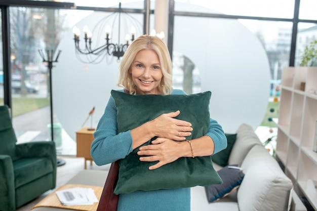 Mulher bonita em uma loja de móveis espaçosa e iluminada, abraçando um travesseiro decorativo verde, de excelente humor. Foto Premium