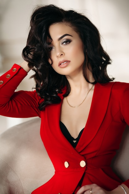 Mulher bonita em vermelho sedutor tocando os lábios à mão. Foto Premium