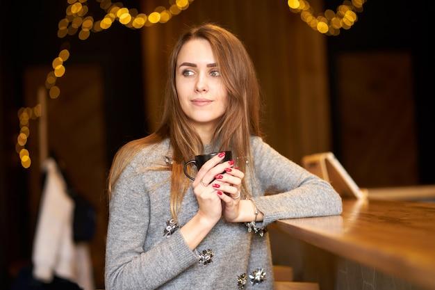 Mulher bonita encantadora atraente, com cabelos longos e sorriso amigável localização no café e segurando a xícara de café preta. Foto Premium