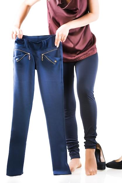 Mulher bonita escolhe a calça certa. conceito de escolher as coisas para o evento desejado da coleção de guarda-roupa Foto Premium