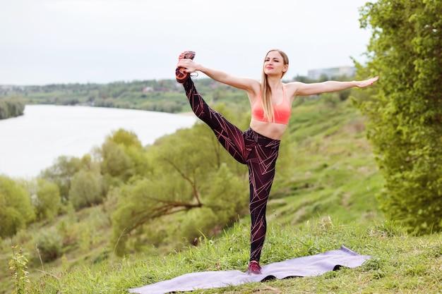 Mulher bonita esportes está esticando a perna enquanto faz exercícios de esporte na margem do rio no verão Foto Premium