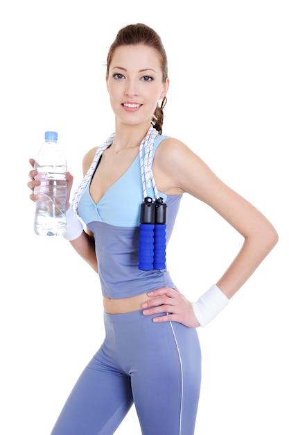 Mulher bonita esportiva com garrafa de água na mão Foto gratuita