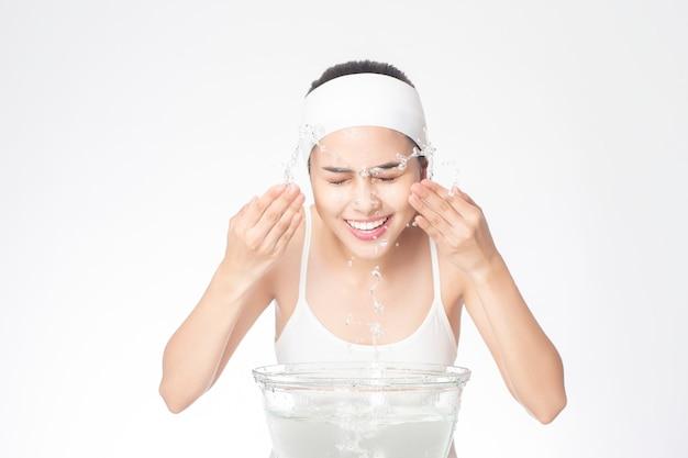 Mulher bonita está lavando o rosto no fundo branco Foto Premium