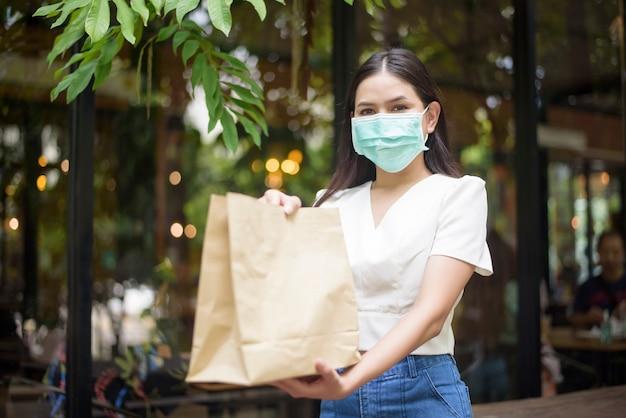 Mulher bonita está recebendo sacola de compras em casa Foto Premium