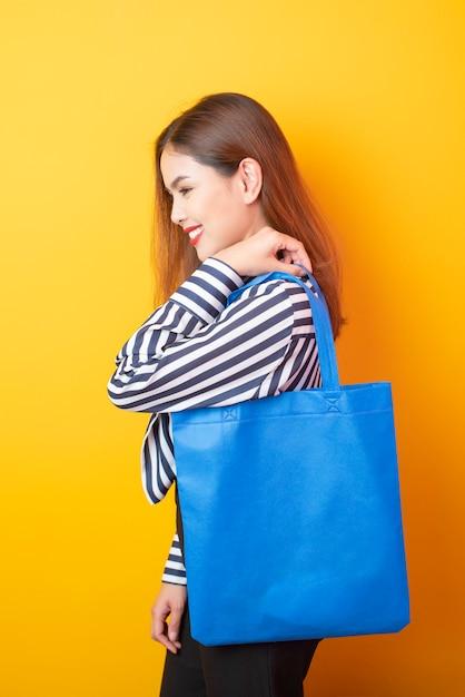 Mulher bonita está segurando o saco de pano azul Foto Premium