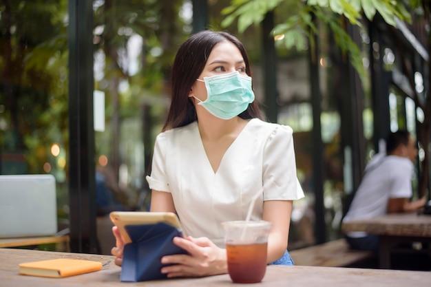 Mulher bonita está usando máscara facial no café Foto Premium