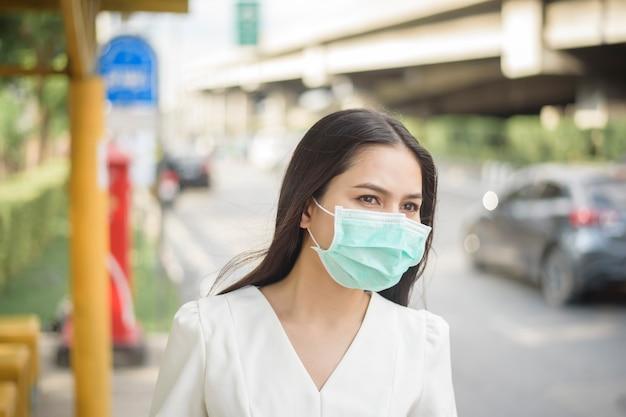 Mulher bonita está usando máscara facial no ponto de ônibus Foto Premium