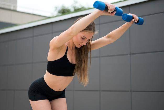 Mulher bonita fazendo alongamentos tiro médio Foto gratuita