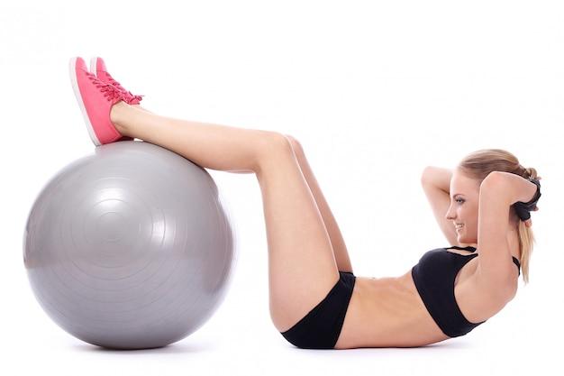 Mulher bonita fazendo exercícios abdominais com bola de fitness Foto gratuita