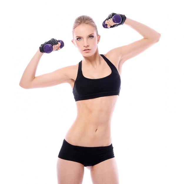 Mulher bonita fazendo exercícios com dumbells Foto gratuita