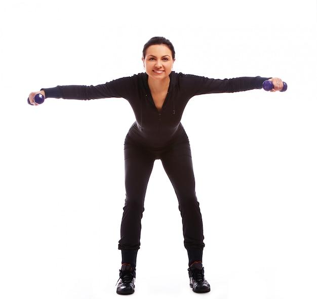 Mulher bonita fazendo exercícios de fitness com pesos Foto gratuita