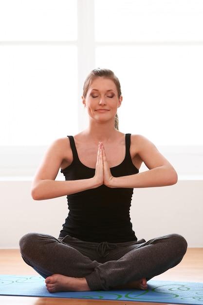 Mulher bonita fazendo exercícios de ioga em casa Foto gratuita