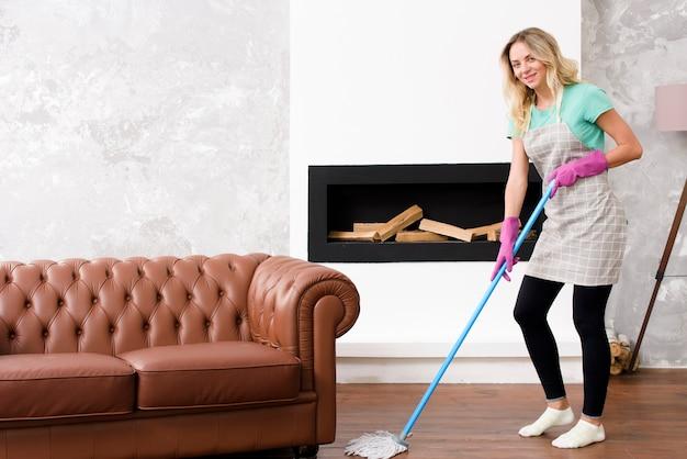 Mulher bonita feliz limpando o chão perto do sofá em casa Foto gratuita