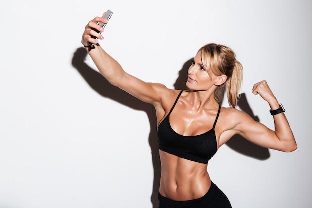 Mulher bonita fitness tomando uma selfie Foto gratuita