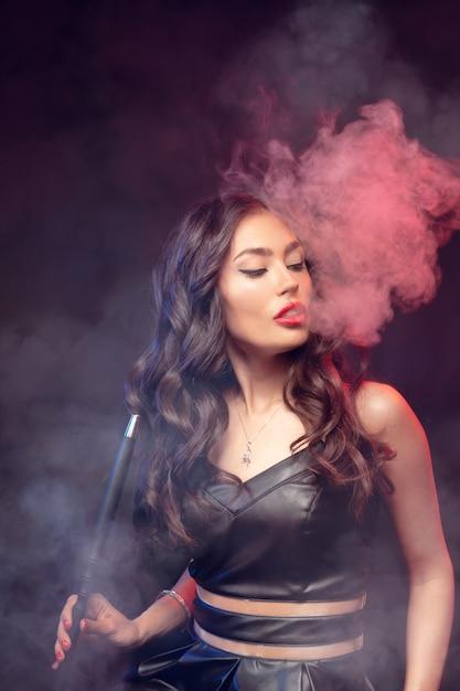 Mulher bonita fuma cachimbo de água ou shisha. vape nuvem branca. Foto Premium