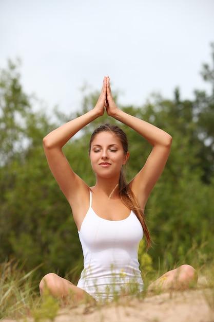 Mulher bonita gosta de ioga na floresta Foto gratuita
