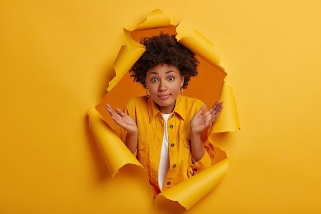 Mulher bonita incerta com penteado afro espalha as palmas das mãos, confunde expressão sem noção que toma decisões, encolhe os ombros não tem ideia de poses em fundo de papel amarelo Foto gratuita