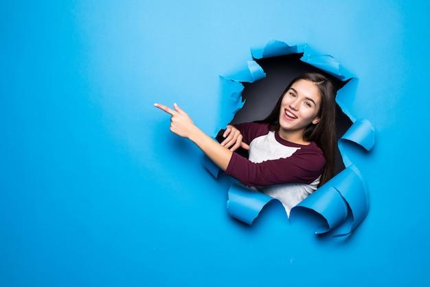 Mulher bonita jovem apontou o lado enquanto olha pelo buraco azul na parede de papel. Foto gratuita
