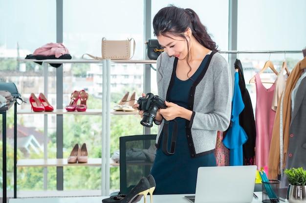 Mulher bonita jovem ásia tirando uma foto e trabalhando compras de comércio eletrônico on-line na loja de roupas. Foto Premium