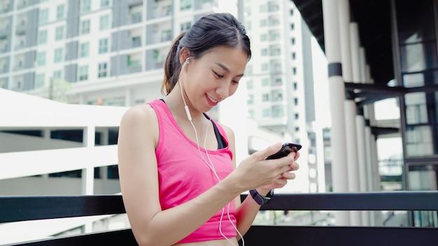 Mulher bonita jovem atleta asiática saudável usando smartphone para ouvir música enquanto corre Foto gratuita