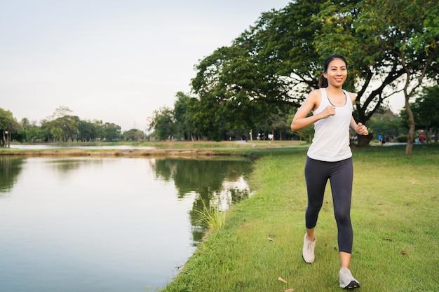 Mulher bonita jovem corredor asiático saudável em roupas esportivas correr e correr Foto gratuita