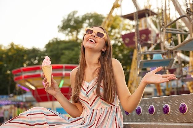 Mulher bonita jovem feliz em um vestido leve romântico sentada sobre as decorações do parque de diversões com casquinha de sorvete na mão, sorrindo com os olhos fechados e levantando a palma da mão Foto gratuita
